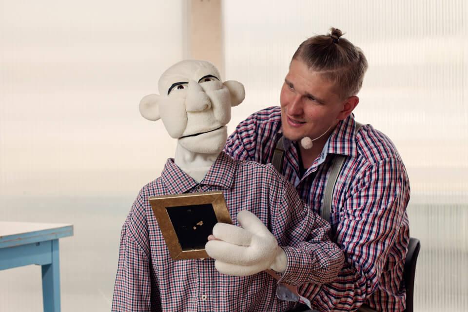 Theaterszene aus Hinter den Fenstern, Puppenfigur Hans-Jürgen schaut auf ein Bild