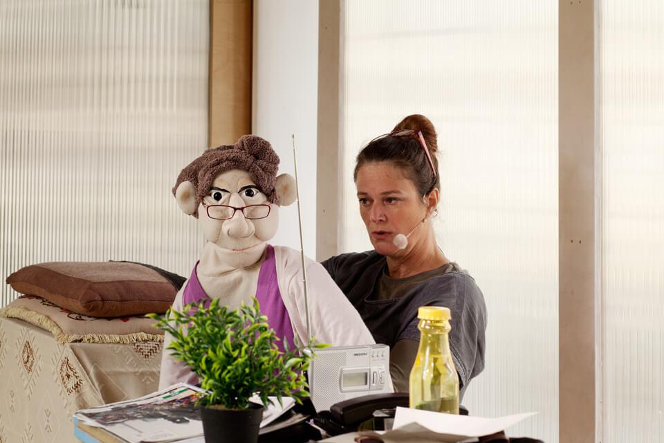 Theaterszene aus Hinter den Fenstern, Puppenfigur Helga schaut zum Publikum