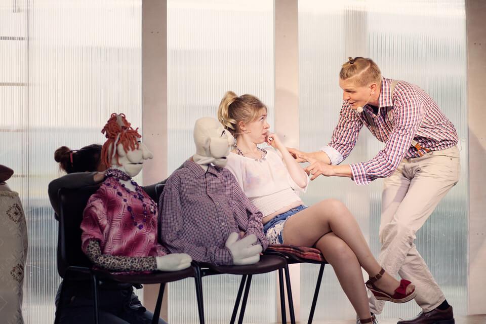 Theaterszene aus Hinter den Fenstern, Figur Raul hat eine Idee und erzählt den Figuren Ilona, Elfi und Hans-Jürgen davon