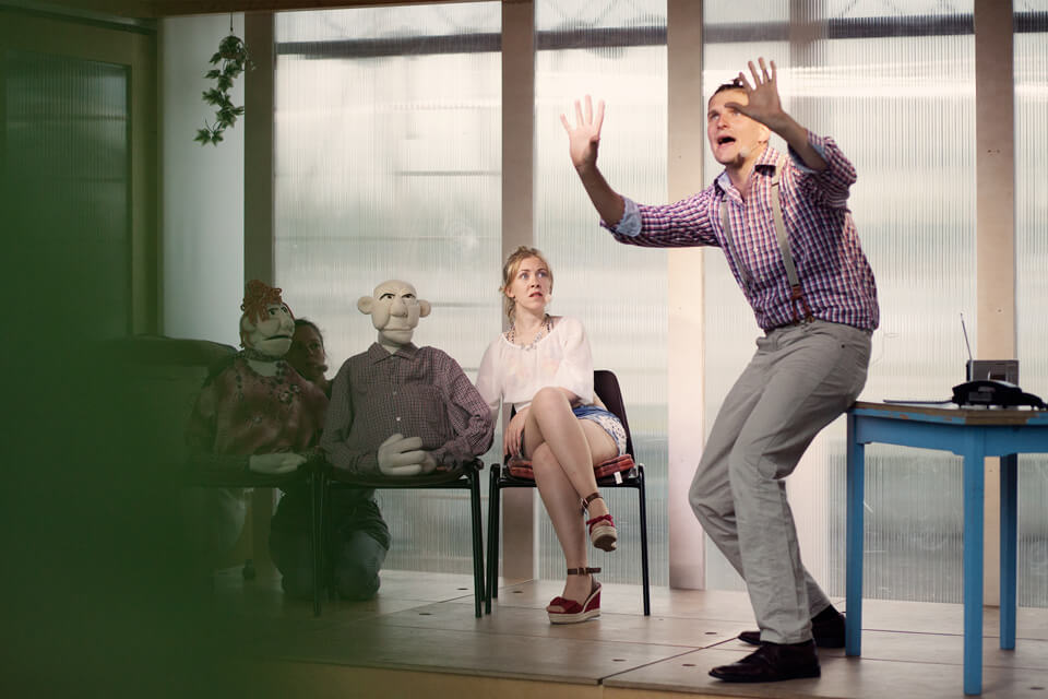 Theaterszene aus Hinter den Fenstern, Figur Raul hebt die Hände abwehrend in die Luft