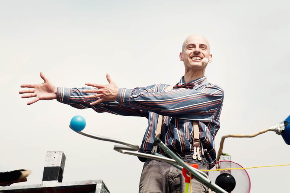 Theaterszene aus Planet Acasio, Figur Eli streckt die Arme zur Seite