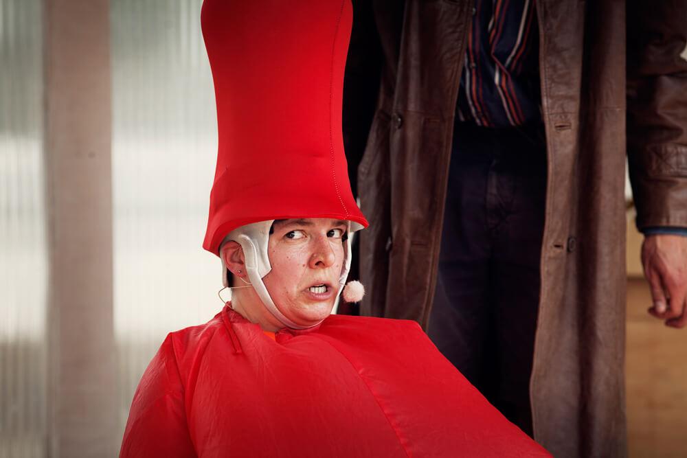 Theaterszene aus Planet Acasio, Figur Wesen in rotem Kostüm mit Zylinderhut schaut verärgert