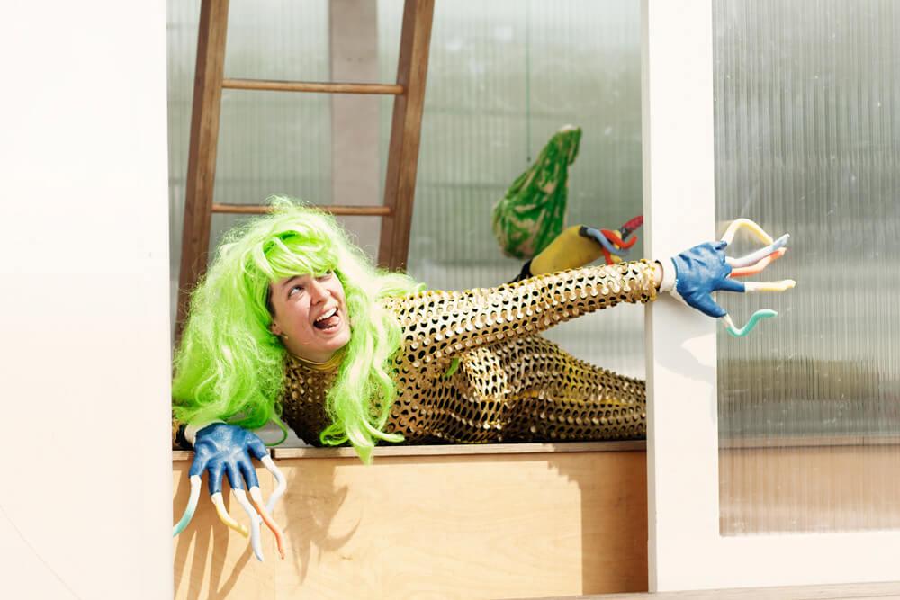Theaterszene aus Planet Acasio, Figur Wesen in goldenem Kostüm und grüner Perücke rekelt sich auf der Bühne