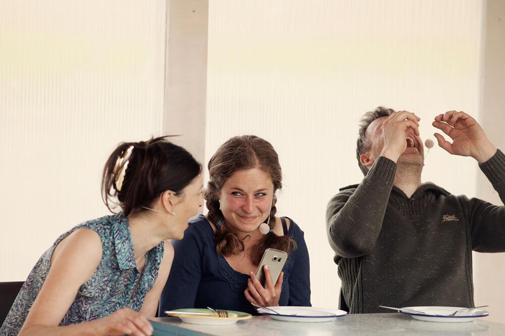 Theaterszene aus Bibergeil, Figuren Biber, Kati und Anke sitzen am Tisch und lachen