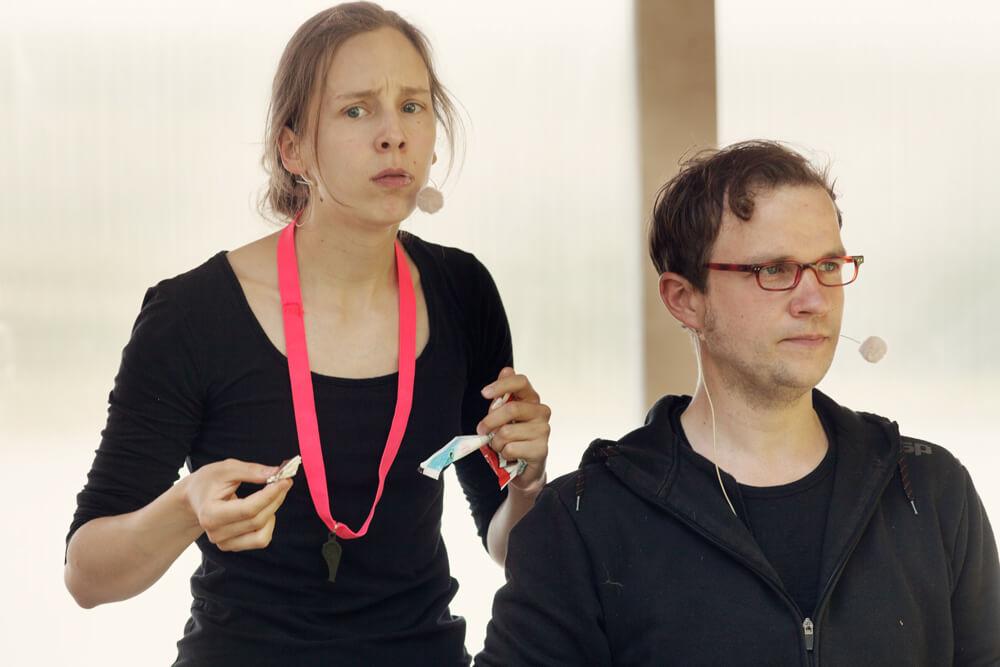 Theaterszene aus Treue Hände, Figuren Sportlehrerin und Dirk essen in der Pause