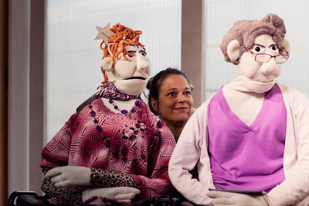 Theaterszene aus Hinter den Fenstern, Puppenfiguren Helga und Efli sitzen nebeneinander