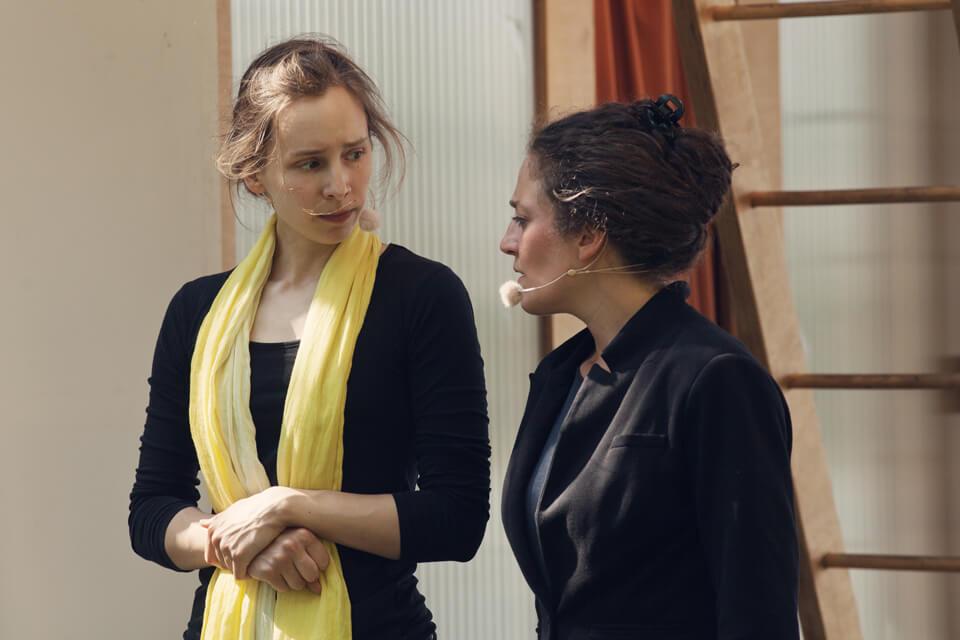 Theaterszene aus Treue Hände, Figuren Gitti und Sylvia unterhalten sich ernst