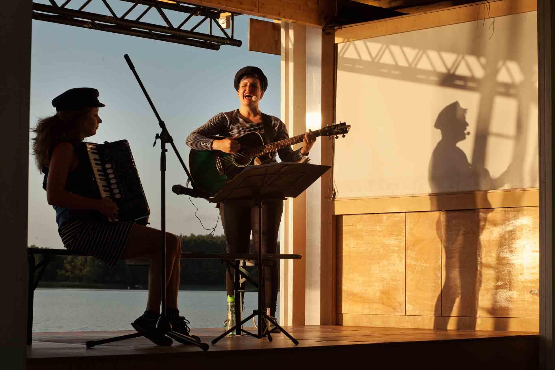Musikerinnen mit Akkordeon und Gitarre machen Ufermusik, Giarristin singt