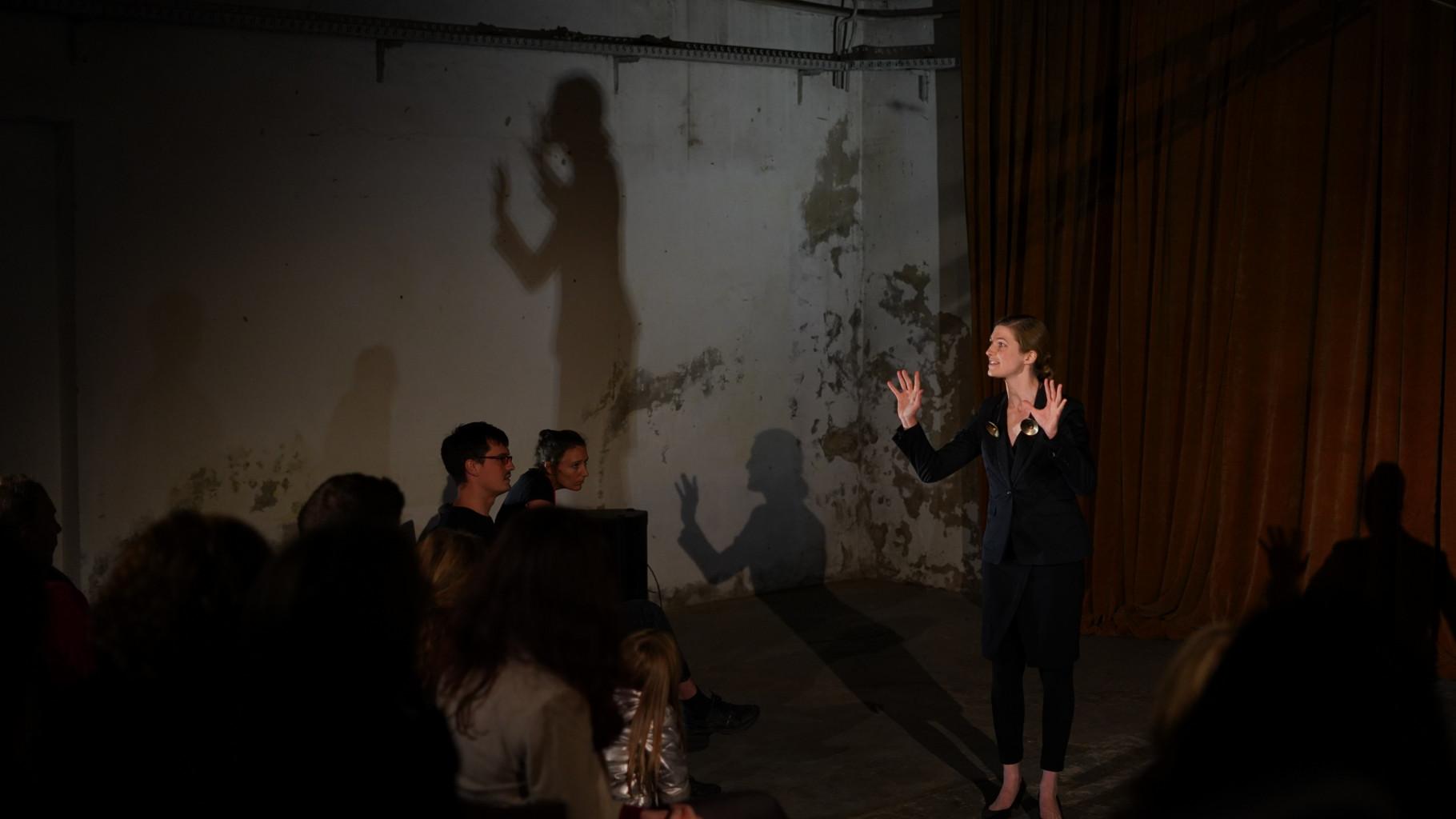 Theaterszene aus Treue Hände, Figur Gitti erklärt den Figuren Sylvia und Dirk ihre Situation