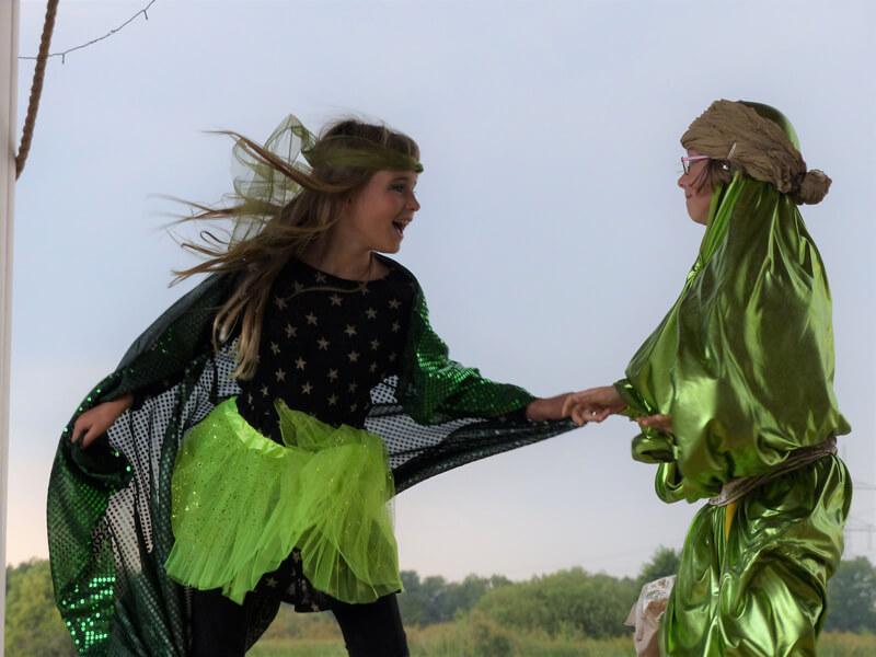 Theatervermittlungsprogramm Theater begegnen, zwei Mädchen in grünen Kostümen spielen zusammen auf der Bühne