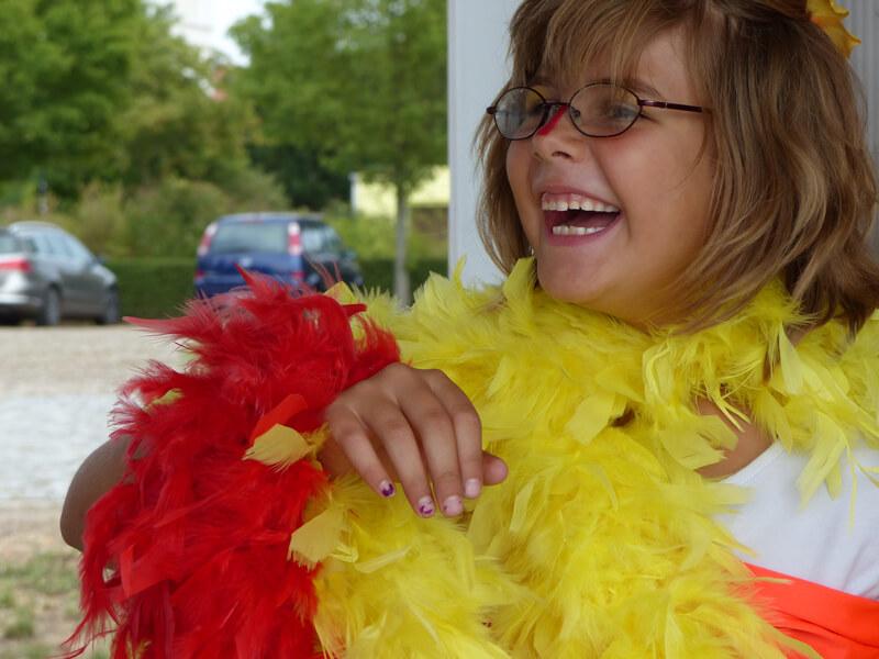 Theatervermittlungsprogramm Theater begegnen, Mädchen mit roter und gelber Federboa lacht