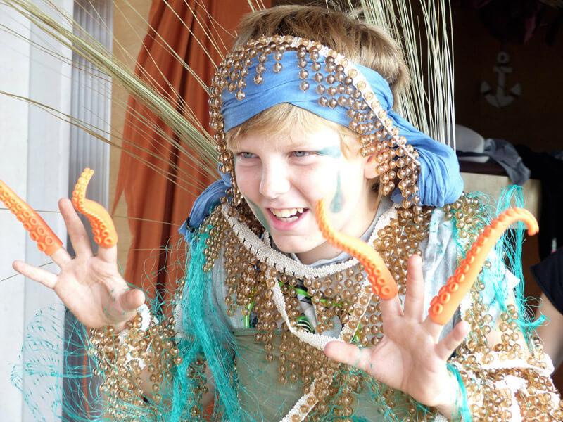 Theatervermittlungsprogramm Theater begegnen, Junge in Kostüm mit Tentakelfingern spielt gruselig