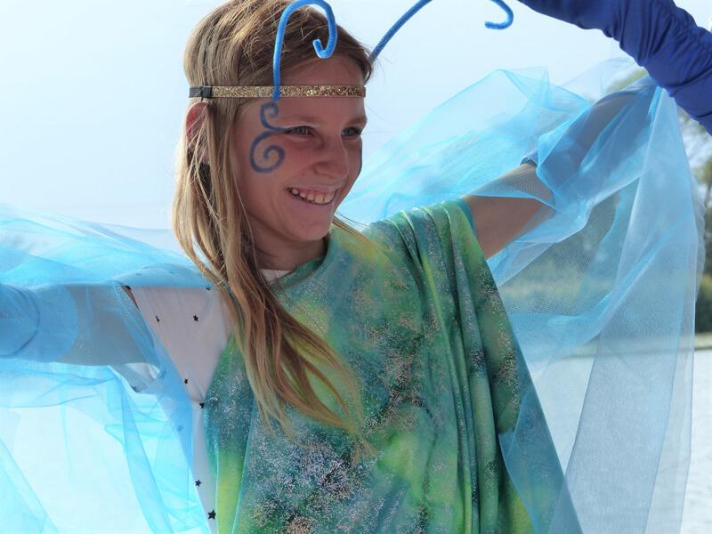 Theatervermittlungsprogramm Theater begegnen, Mädchen in blauem Kostüm mit bemaltem Gesicht lacht