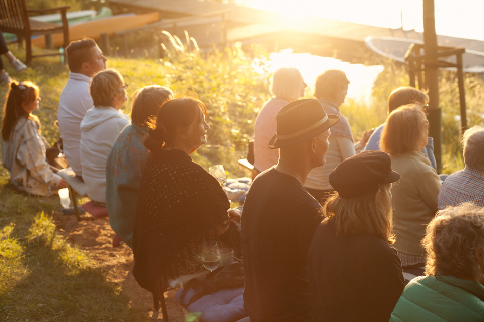 Publikum sitzt im Sonnenuntergang bei Ufermusik