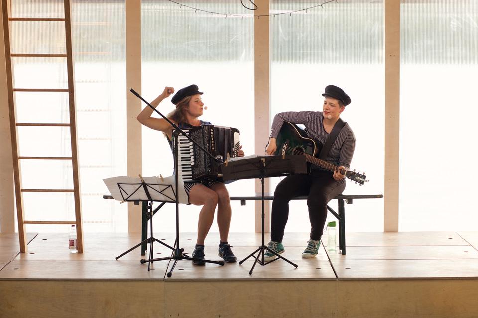 Musikerinnen mit Akkordeon und Gitarre machen Ufermusik, Akkordeonistin gibt den Einsatz