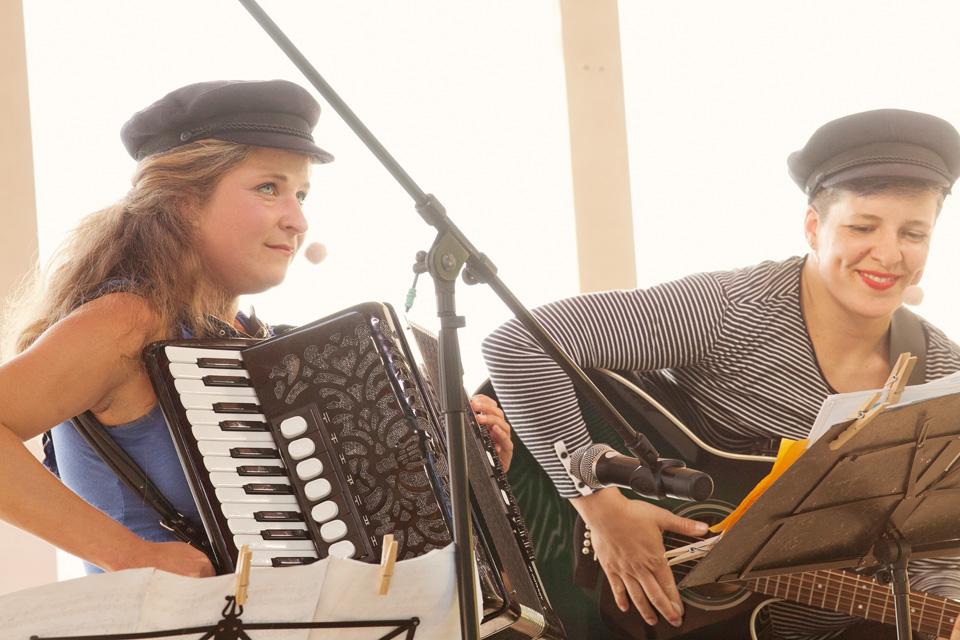 Musikerinnen mit Akkordeon und Gitarre machen Ufermusik