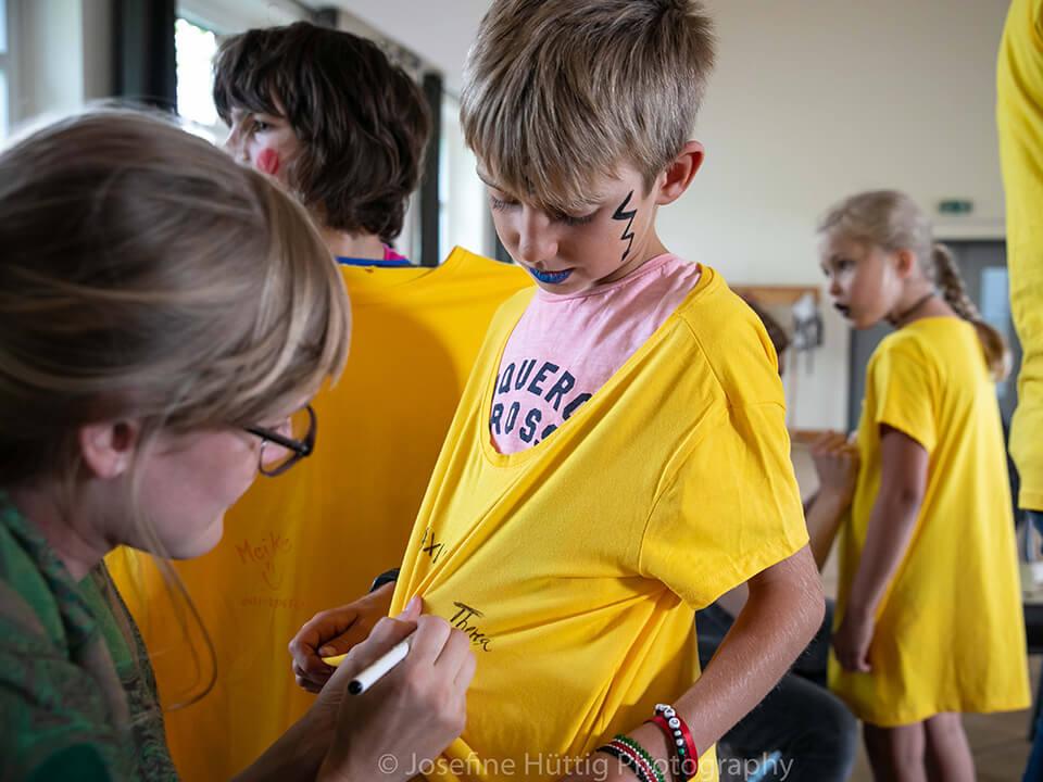 Theatervermittlungsprogramm Theater begegnen, Frau malt einem Jungen auf das gelbe Tshirt