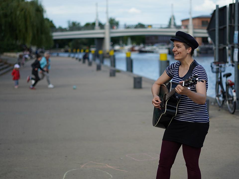 Musikerin mit Gitarre macht Ufermusik und lacht