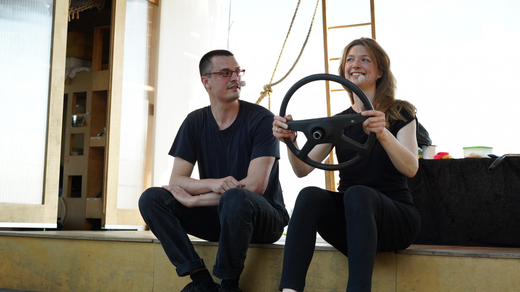 Theaterszene aus Treue Hände, Figuren Dirk und Gitti fahren Auto