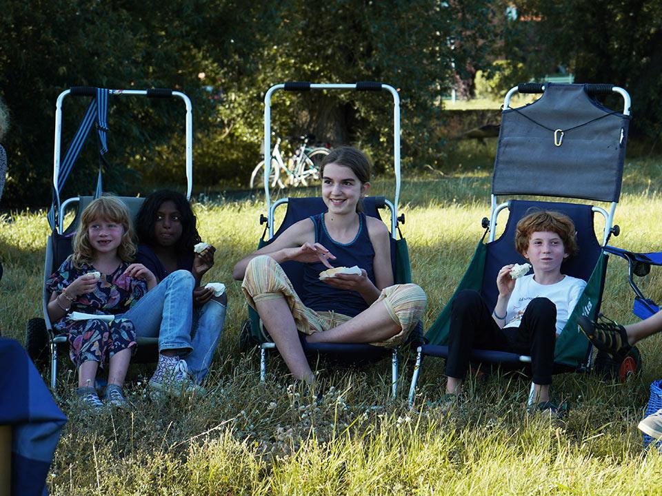 Workshop Nachbarschaftstheater in Strodehne, Kinder stehen sitzen in Klappstühlen