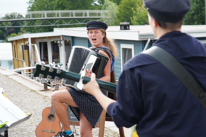 Musikerinnen mit Akkordeon und Gitarre machen Ufermusik, Akkordeonistin singt