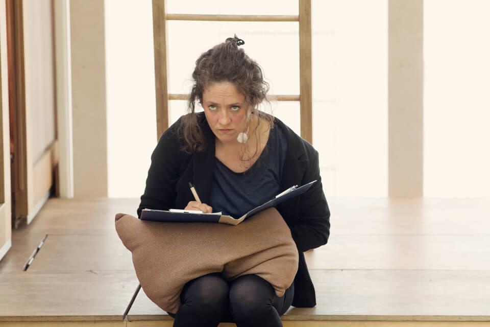 Theaterszene aus Treue Hände, Figur Gitti ist wütend und schreibt in einen Hefter