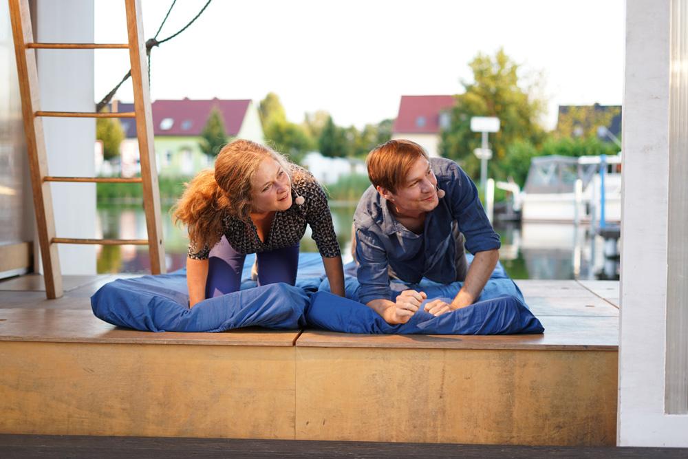 Theaterszene aus Durch den Wind, Figuren Paula und Lucas schauen aus dem Hausboot