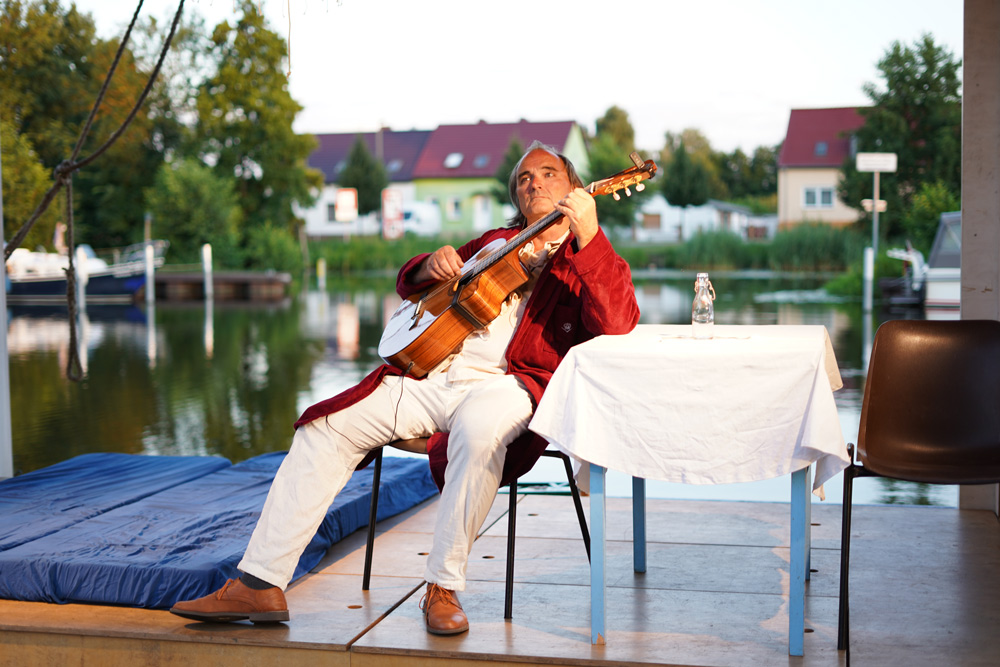 Heinrich spielt Gitarre im roten Bademantel