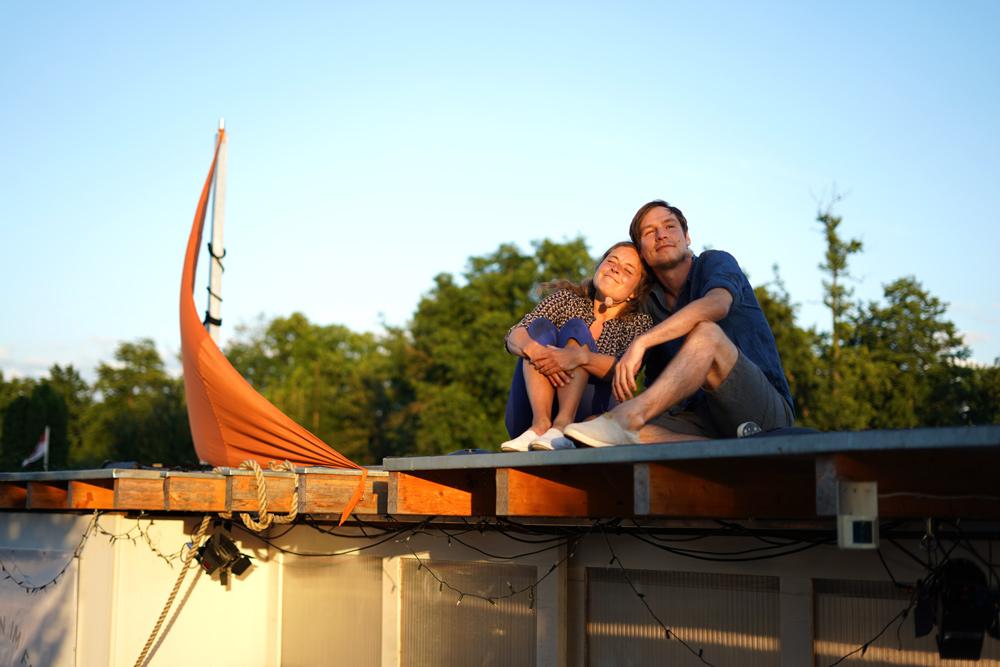 Theaterszene aus Durch den Wind, Figuren Paula und Lucas sitzen zusammen auf dem Dach ihres Hausbootes