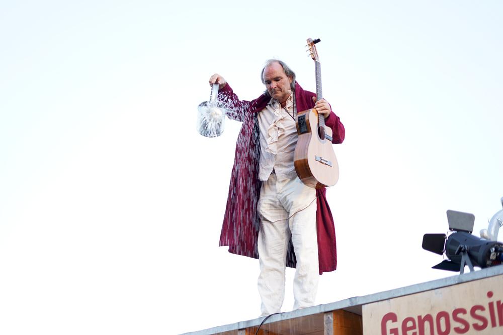 Theaterszene aus Durch den Wind, Figur Heinrich lässt es mit einer Gießkanne regnen
